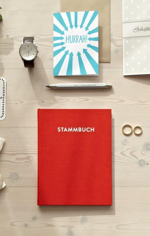 Stammbuch Paul rubinrot auf einem weißen Tisch mit Glückwunschkarten, Kohlestift und Eheringen