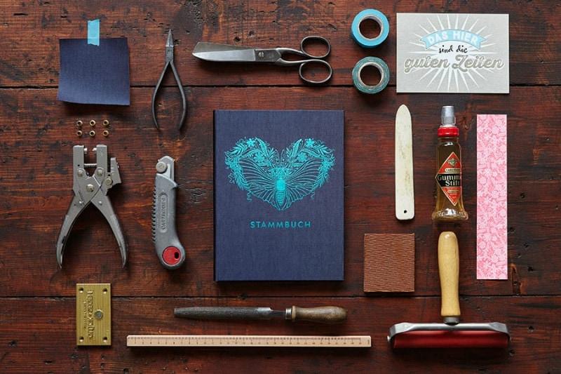 Ein Stammbuch Greta in Oxfordblau auf einem alten dunklen Holztisch mit Utensilien wie Schere, Lochzange, Falzbein und Gummilösung.