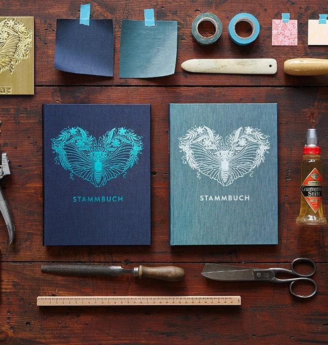 Stammbücher Greta Oxfordblau und Greta Kobalttürkis auf einer alten Holzplatte mit Falzbein, Gummierstift, Reibahle