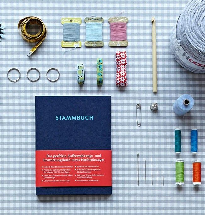 Stammbuch Paul Nachtblau auf einem karierten Tisch mit Maßband, Nähgarn, Häkelnadel und ähnlichem