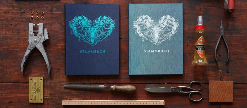 Stammbücher Greta in Oxfordblau und Kobalttürkis auf einer dunklen Holz-Tischplatte umgeben von Lochzange, Gummierstift, Schere, Prägestempel, Feile.