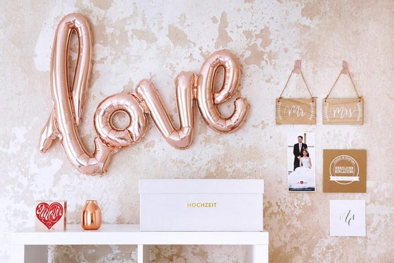 Ein Hochzeitsarchiv Clara auf einem Kallax-Regal vor einer Wand mit einem kupferfarbenen love-Ballon und anderen Accessoires in Kupferton.