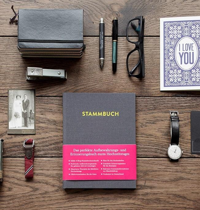 Stammbuch Paul Platingrau auf Eichentisch mit Füllfederhalter, Moleskine Büchern, Brille, Uhr