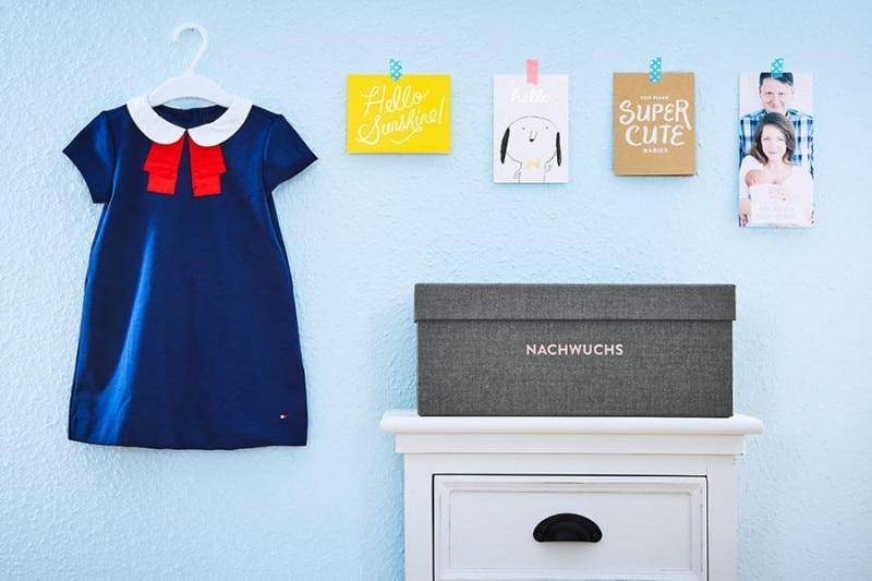 Nachwuchs-Archivbox Philipp auf einem weißen Schränkchen vor himmelblauer Wand.An der Wand hängt ein Kleidchen und Glückwunschkarten.