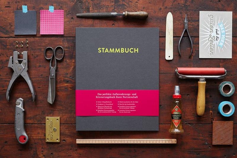 Ein DIN A4 Stammbuch Caspar in Platingrau auf einem alten dunklen Holztisch mit Utensilien wie Schere, Lochzange, Falzbein und Gummilösung.
