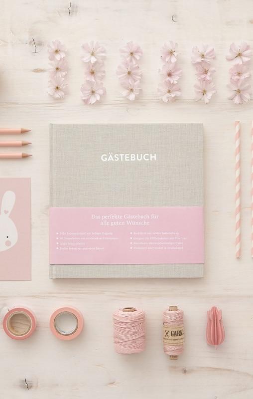 Gästebuch Hugo Cremebeige mit rosafarbenen Gegenständen wie Garn, Klebeband, Strohhalmen auf einem weißen Tisch