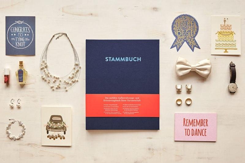 Ein DIN A4 Stammbuch Caspar in Nachtblau auf einem hellen Birkenholztisch mit Gegenständen wie einer weißen Fliege, einer Max Bill Uhr, Eheringen und Manschettenknöpfen..
